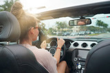 Young woman driving convertible car