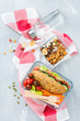 Lunch box with sandwich, fruits, vegetables, nut mix and water - 246178822