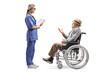 Leinwandbild Motiv Young female nurse talking to an elderly gentleman in a wheelchair