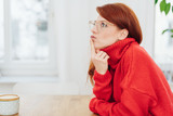 Thoughtful redhead woman wearing glasses