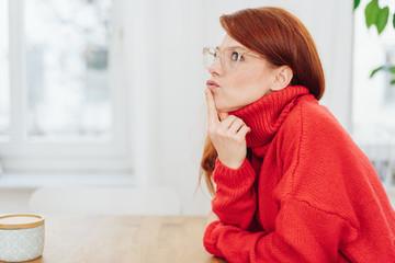 Thoughtful redhead woman wearing glasses