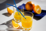 Freshly squeezed orange juice in glass cups, blue napkin and fresh oranges.