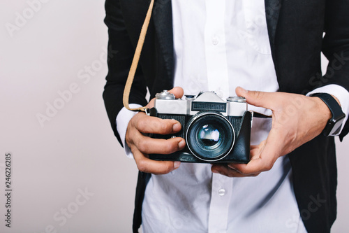 aec9d087abdb5 Stylish image of retro camera in hands of handsome guy in suit. Leisure