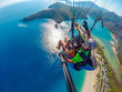 Quadro Paraglider tandem flying over the sea with blue water and mountains in bright sunny day. Aerial view of paraglider and Blue Lagoon in Oludeniz, Turkey. Extreme sport. Landscape