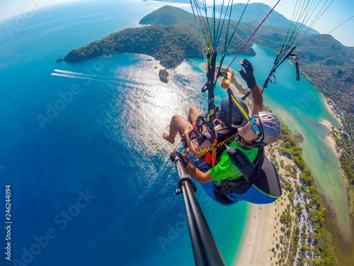 Paraglider tandem flying over the sea with blue water and mountains in bright sunny day. Aerial view of paraglider and Blue Lagoon in Oludeniz, Turkey. Extreme sport. Landscape