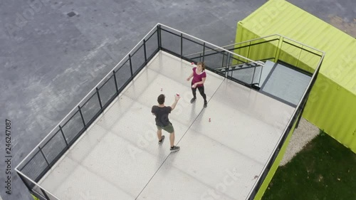 aerial view of a male and female teenager juggling with balls outdoors