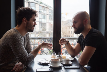 Two young guys with beards drink a coffee and having a nice conversation.