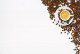 White wooden table with espresso cup and coffee beans. Flat lay.