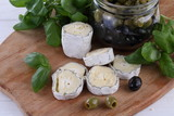 Still-life with saint-mor-de-turen cheese with black olives on white background - 246254232