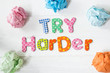 Try harder motivational advice with various colored letters on white wooden table or background