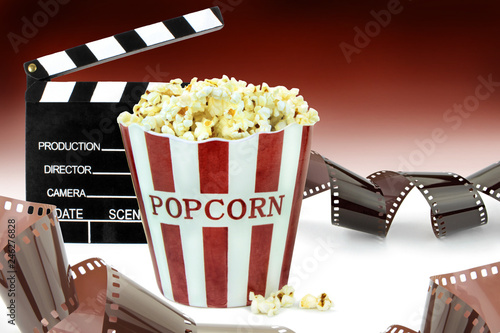 Leinwanddruck Bild Popcorn, movie clapper and film strips.  Cinema concept image