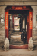 """Open gates to Hutong. A sign on both sides of the entrance reads """"Welcome"""", as well as a wish for happiness and good luck at home. Beijing, China."""