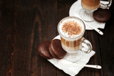 Coffee in glass on the wooden background.  A glass with cappuccino and cinnamon.  - 246308260