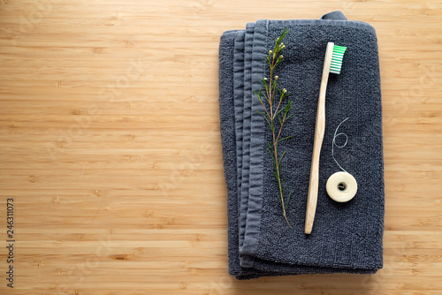 eco natural bamboo toothbrushes and biodegradable silk dental floss on the black towel, sustainable lifestyle concept. zero waste home. bathroom essentials, plastic free items