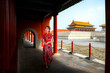 Chinese lady walk in red cheongsam dress in ancient Chinese forbidden palace