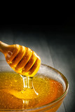 Honey with gold color flows down from a spoon. Healthy food concept. Healthy eating. Diet. Selective focus. Background with copy space.