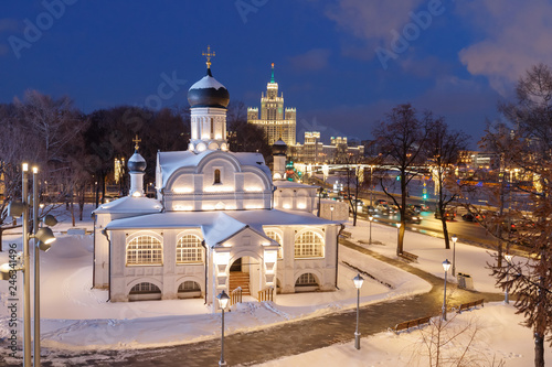 View to the white stone church in Zaryadye Park and iconic skyscraper in Moscow, Russia. Winter time, blue hours.
