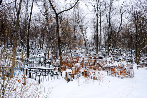 View of the graveyard almost abandoned in suburbs of Moscow with snow trees during winter.