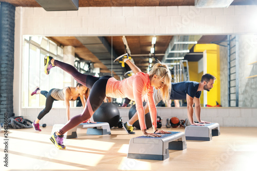 Group of people with healthy habits doing exercises for legs on steppers. Gym interior. In background mirror with their reflection. © dusanpetkovic1