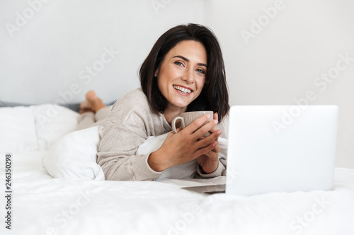 Leinwandbild Motiv Photo of middle-aged woman 30s using laptop, while lying in bed with white linen in bright room