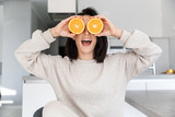 Image of funny woman 30s holding two pieces of orange, while sitting in living room - 246350692