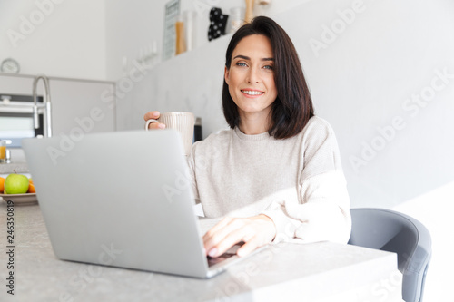 Leinwandbild Motiv Image of attractive woman 30s working on laptop, while sitting over white wall in bright room