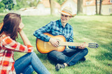 Happy young couple in love outdoors on picnic having a good leisure vacation together in cowboy style. Boyfriend playing the guitar for girlfriend outdoors