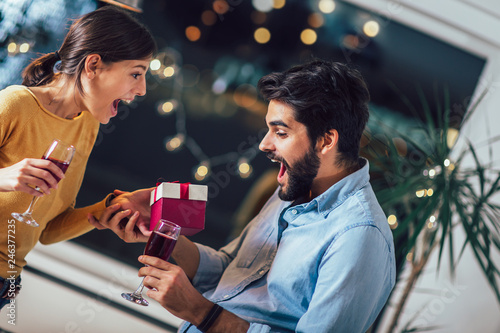 Leinwandbild Motiv Beautiful young couple is celebrating at home. Pretty girl is giving her boyfriend a gift box
