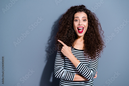 Leinwandbild Motiv Portrait of her she nice-looking cute crazy fascinating attractive lovely cheerful cheery wavy-haired lady in striped pullover pointing aside ad opened mouth isolated over gray pastel background