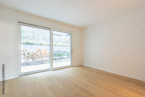 Empty room with parquet and window with garden view - 246418824