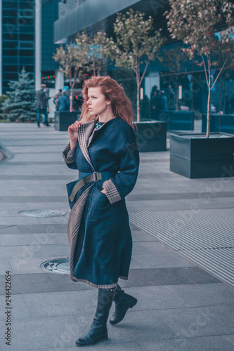 fototapeta na ścianę Confident attractive modern elegant woman in a long coat with thick long hair in the wind