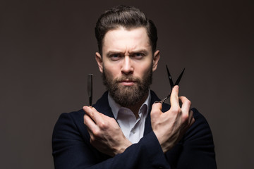 Bearded young man caucasian hipster with moustache holding scissors and straight razor on gray background. Mens haircut, shaving. Male in barbershop.