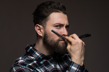 Handsome hipster man with long beard hold a razor vear the face wear in plaid shirt isolated on gray background