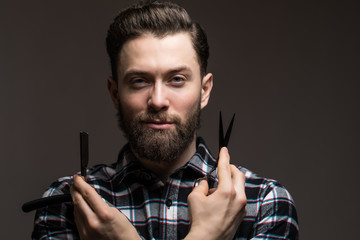 Handsome bearded young man in a plaid shirt holding a sharp professional scissors and razor isolated on dark background. Close-up