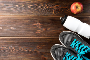 Fitness sneakers, bottle of water and red apple on wooden background.