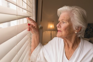 Senior woman looking through window blinds