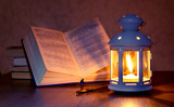 Reading a book at the light of a lantern. Lantern with a lit candle near the unfolded book_ - 246478272