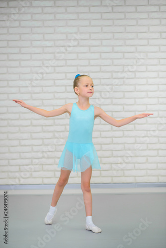 Little ballerina in blue dress and pointe shoes is dancing in ballet school. Cute girl in dance class. © SergeyCash