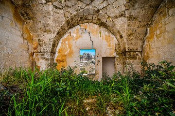View through a window in a medieval, cracked stone wall of the ancient Madonna de Idris rock church and the Sassi of Matera, Italy, in the Basilicata region.