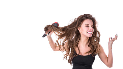 cute girl pulls out a comb from tangled hair and screams into the camera on a white background. Hair health concept