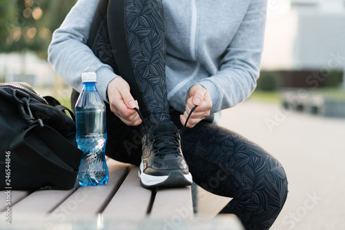 Shot of athletic woman tying she is shoelaces before a run. © LMproduction