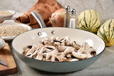 Raw sliced mushrooms in a skillet