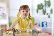 Leinwandbild Motiv Portrait of joyful child girl toying with statuette of animals in nursery or kindergarten