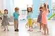 Leinwanddruck Bild - Group of expressive preschool children with raising hands while having fun in entertainment center