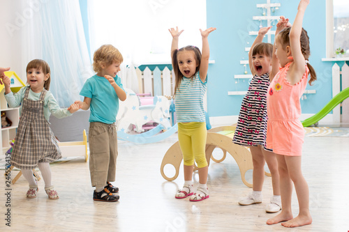 Group of expressive preschool children with raising hands while having fun in entertainment center - 246553435