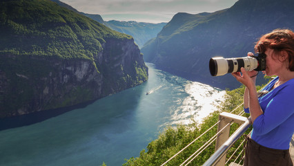Tourist taking photo of fjord landscape, Norway