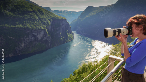 Foto Murales Tourist taking photo of fjord landscape, Norway