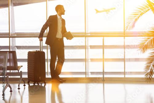 Leinwanddruck Bild Geschäftsmann auf Reisen am Flughafen im Sommer