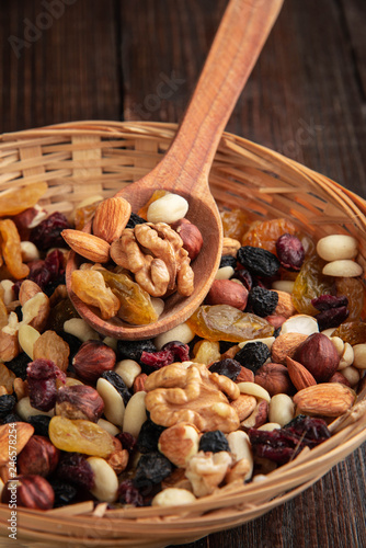 fototapeta na ścianę Dried fruits and nuts on a wooden background in a wicker basket with a wooden spoon