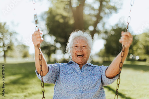 Leinwanddruck Bild Cheerful senior woman on a swing at a playground